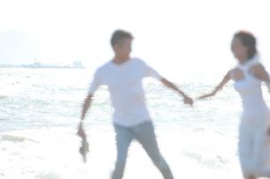 海辺で裸足で戯れるカップルの写真素材 [FYI02829334]