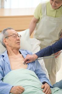 介護ベッドの老人を診察する医者と介護ヘルパーの写真素材 [FYI02829357]