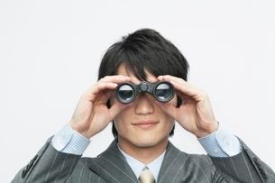 双眼鏡をのぞくビジネスマンの写真素材 [FYI02829373]