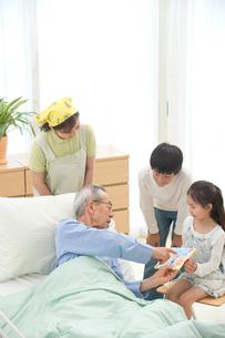 介護ベッドの老人と絵を見せる孫と介護ヘルパーの写真素材 [FYI02829420]