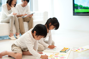リビングでお絵描きをする子供男女の家族の写真素材 [FYI02829467]