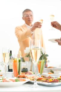 シャンパンで乾杯する中高年男性とホームパーティーのお客様の写真素材 [FYI02829474]