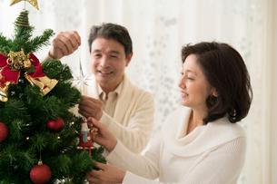 Xmasツリーに飾り付けする中高年夫婦の写真素材 [FYI02829516]