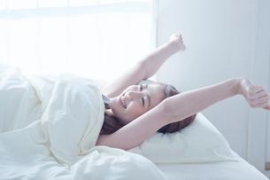 ベッドで手を伸ばす笑顔の女性の写真素材 [FYI02829525]