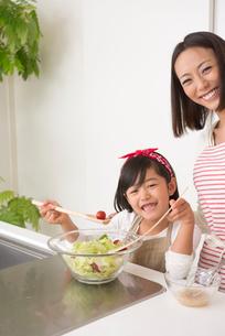 キッチンで料理する母と女の子の写真素材 [FYI02829567]