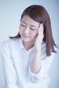 目を閉じて頭に手をあてる女性の写真素材 [FYI02829598]
