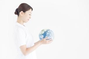 地球を見つめる看護師の写真素材 [FYI02829614]