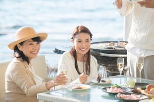 海岸のレストランでバーベキューする家族の写真素材 [FYI02829650]
