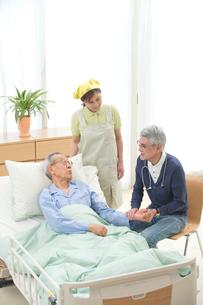 介護ベッドの老人を診察する医者と介護ヘルパーの写真素材 [FYI02829655]