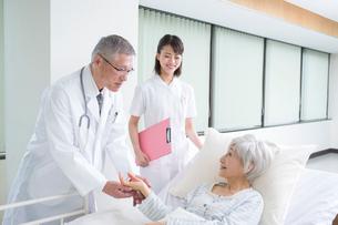 ベッドの入院シニア女性患者を診察する医者と看護師の写真素材 [FYI02829681]
