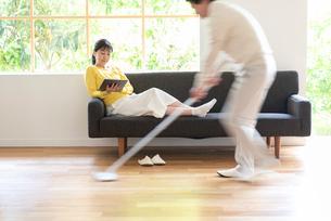 掃除する男性とソファでPCを見る中高年女性の写真素材 [FYI02829754]