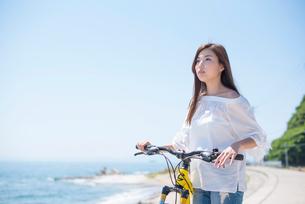海の堤防で自転車の女性の写真素材 [FYI02829769]