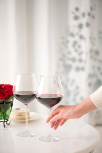 赤ワインのグラスを持つ女性の手の写真素材 [FYI02829803]