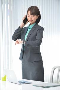 立って携帯電話してウェアラブルウォッチを見るOLの写真素材 [FYI02829825]