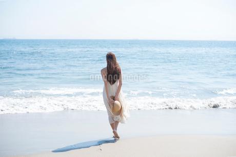 海の砂浜を素足で散歩する女性の写真素材 [FYI02829841]