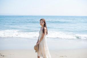 海の砂浜を素足で散歩する女性の写真素材 [FYI02829858]