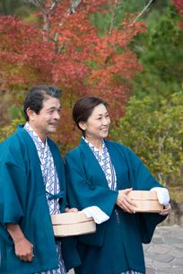 秋の温泉旅館で浴衣の桶と手拭を持つ中高年夫婦の写真素材 [FYI02829956]