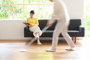 掃除する男性とソファでPCを見る中高年女性の写真素材 [FYI02829958]