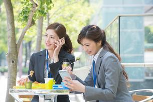 弁当を食べスマホを見て電話するOL2人の写真素材 [FYI02829960]