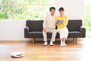 お掃除ロボットとソファでPCを見る中高年夫婦の写真素材 [FYI02829975]