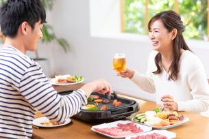 生ビールで焼肉を食べる30代夫婦の写真素材 [FYI02829980]