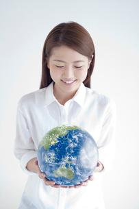 地球を見つめる笑顔の女性の写真素材 [FYI02830057]