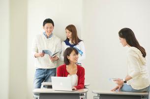 講義室で談笑する大学生男女四人の写真素材 [FYI02830066]
