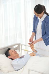 病院ベッドの老人に体温計を渡す看護師の写真素材 [FYI02830124]