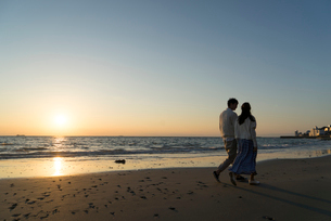 夕日の海岸を散歩するカップルの写真素材 [FYI02830130]