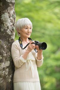 一眼レフカメラで写真を撮るシニア女性の写真素材 [FYI02830251]