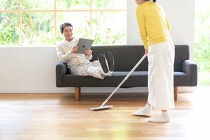 掃除する女性とソファでPCを見る中高年男性の写真素材 [FYI02830306]