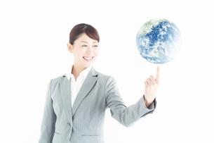 地球を見つめる笑顔のビジネスウーマンの写真素材 [FYI02830311]