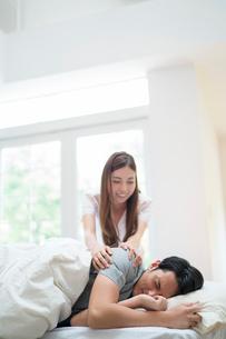 寝てる男性を起こすパジャマの女性の写真素材 [FYI02830375]