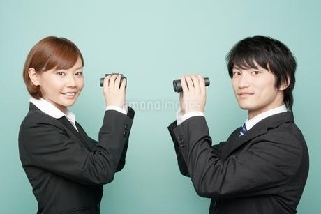 双眼鏡を持つビジネスマンとビジネスウーマンの写真素材 [FYI02830397]