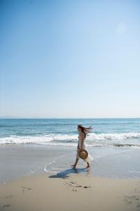 海の砂浜を素足で散歩する女性の写真素材 [FYI02830403]
