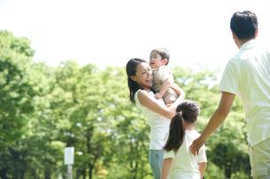 芝生の公園で遊ぶ四人家族の写真素材 [FYI02830434]
