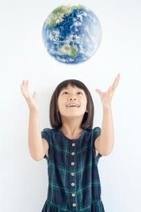 地球を見上げる女の子の写真素材 [FYI02830490]
