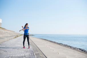 海の堤防でストレッチする女性の写真素材 [FYI02830494]