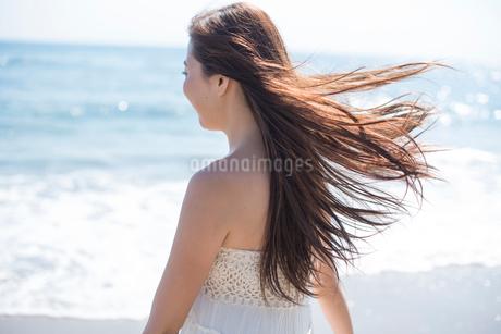 海の砂浜を素足で散歩する女性の写真素材 [FYI02830501]