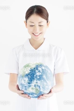 地球を見つめる笑顔の看護師の写真素材 [FYI02830513]