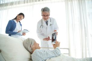 病院ベッドの老人を診察する医者と看護師の写真素材 [FYI02830659]