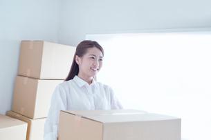 段ボール箱を持つ笑顔の女性の写真素材 [FYI02830747]