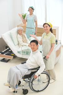 介護ベッドと車椅子の老人と案内する介護ヘルパーの写真素材 [FYI02830832]