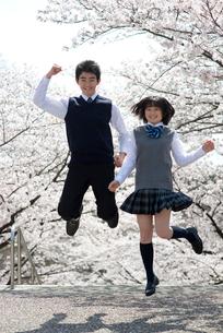 桜とジャンプする男女高校生の写真素材 [FYI02830848]