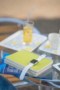 テーブルに置かれた教科書とウェアラブルウォッチの写真素材 [FYI02830863]