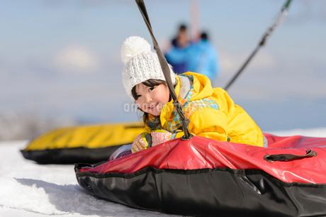 雪上で遊具で遊ぶ子供の写真素材 [FYI02831154]