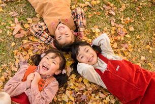 紅葉の公園で落ち葉の上に寝そべる女の子の写真素材 [FYI02831297]