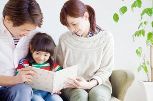 寄り添い絵本を読む家族の写真素材 [FYI02831540]