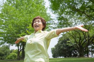 手を伸ばす笑顔のシニア女性の写真素材 [FYI02831624]