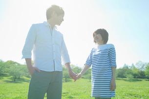 手をつなぎ見つめ合う笑顔のカップルの写真素材 [FYI02832053]